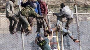 Les gardes civils espagnols tentent de déloger des migrants assis sur le grillage, frontière entre le Maroc et l'enclave de Ceuta (photo d'archives).