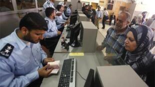A Hamas policem officer checks the passport of a Palestinian passenger at the Rafah border crossing