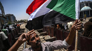 A Sudanese protester waves a national flag as he flashes the V for victory sign during a protest near the army headquarters in the capital Khartoum