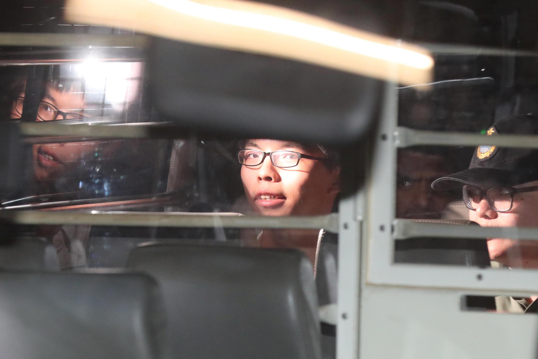 2017年8月17日,雨伞运动学生领袖黄之锋(中)与罗冠聪(左)被押上狱方车辆离开法院。