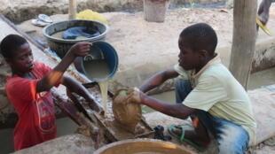 Deux enfants âgés de 9 et 12 ans, qui travaillent quotidiennement dans une mine d'or artisanale dans le centre du Ghana.