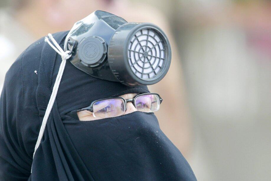 Phong trào Huynh đệ Hồi giáo ra đời năm 1928, tại Ai Cập, chủ trương một Nhà nước thần quyền, là mối đe dọa với nhiều vương quốc Sunni. Trong ảnh : Một thành viên Huynh đệ Hồi giáo mang mặt nạ chống hơi cay cùng khăn trùm niqab. REUTERS