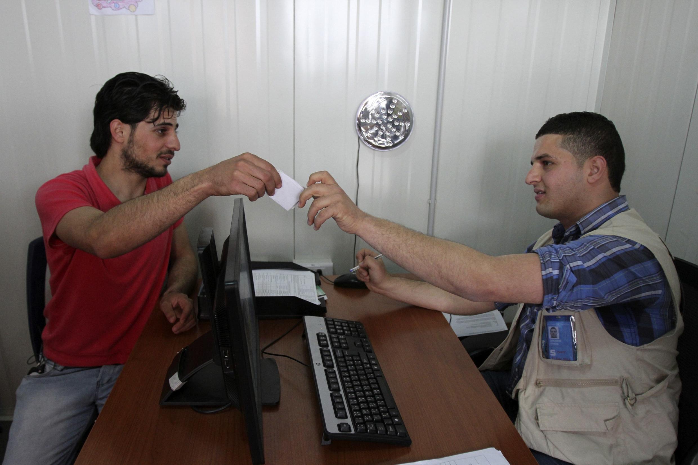 Yehya Chaker Charkieh é milionésimo refugiado sírio no Líbano. Aqui, com um representante do Alto Comissariado das Nações Unidas para os Refugiados (ACNUR) em Tripoli, 3 de abril de 2014.