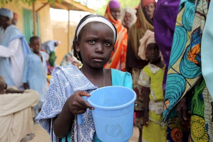 Wata yarinya dauke da ruwan sha, yayinda mata da rikicin Boko Haram ya raba da muhallansu, suka yi layi don karbar bargunan rufa daga sojojin Najeriya a garin Damasak dake Borno. 24/3/2015.