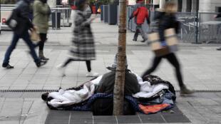 Dans une rue à Lyon, des passants marchent à côté d'un sans-abri alors que la température est en-dessous de 0°C.