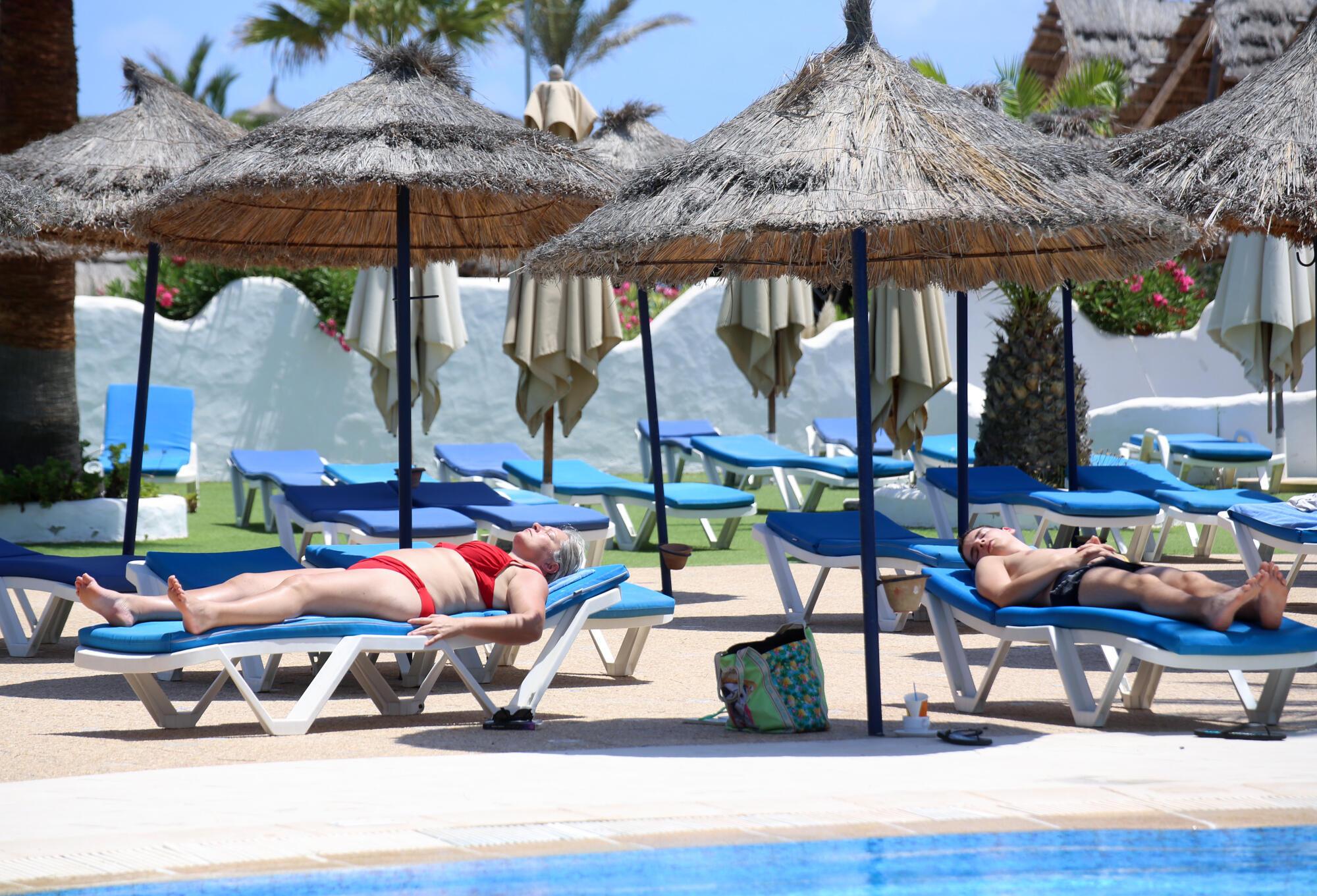 Des touristes européens profitent du soleil au bord de la piscine d'un hôtel sur l'ile de Djerba, en Tunisie le 18 juillet 2020