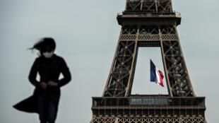 Una mujer con mascarilla camina por París, con la Torre Eiffel de fondo, el 11 de mayo de 2020