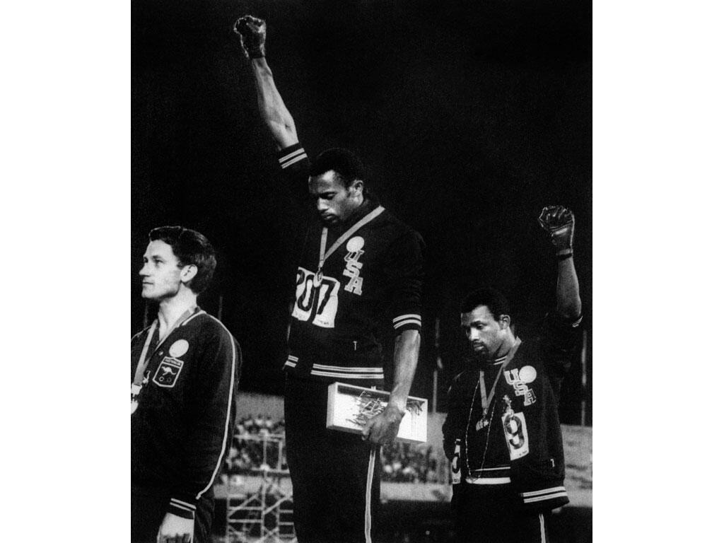 Sur le podium des Jeux Olympiques de Mexico en 1968, à l'issue de la finale du 200 m, les athlètes noirs Tommie Smith et John Carlos lèvent un poing ganté de noir, en référence à la ségrégation aux Etats-Unis.