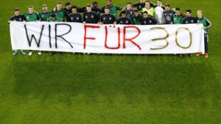"""Les joueurs allemands déploient une banderole """"Nous pour les 30"""", faisant une allusion aux 30 articles de la Charte des droits humains des Nations unies, et addressée au Qatar, hôte du prochain Mondial, avant leur match de qualifications contre la Macédoine du Nor, le 31 mars 2021 à Duisbourg"""