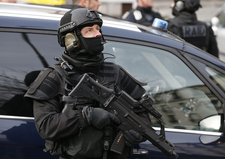 Сотрудник элитного подразделения французской полиции RAID во время визита премьер-министра Израиля Беньямина Нетаньяху в кошерный магазин, подвергшийся атаке террориста в Париже, 12 января 2015 г.