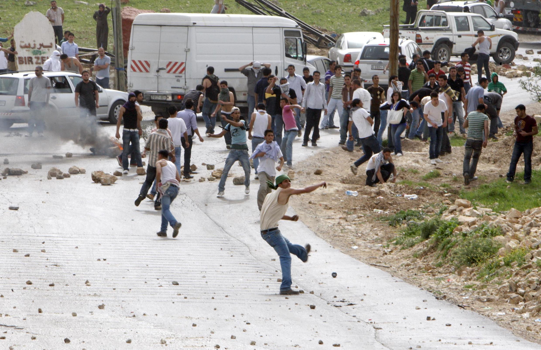 Palestinians throw stones at police at the Atara crossing, north of Ramallah