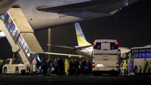 Les passagers du navire de croisière «Diamond Princess», montent à bord des deux avions affrêtés par les États-Unis à l'aéroport de Haneda à Tokyo, le 17 février 2020.