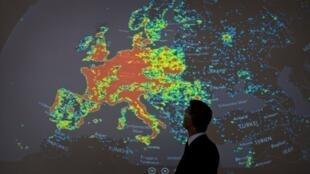 Un homme devant une carte de l'Europe présentant les activités de botnets (machines zombies).