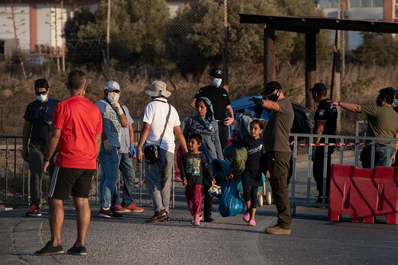Une famille de migrants arrive devant un camp provisoire après la destruction de celui de Moria sur l'île grecque de Lesbos.