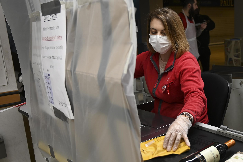 Uma empregada de um supermercado usando máscara trabalha protegida por um filme plástico durante a quarentena, em Estrasburgo, no leste da França, em 19 de março de 2020.