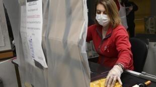 2020年3月19日,在斯特拉斯堡的一家超市里,一名收银员戴着口罩,在塑料布防护后,工作。