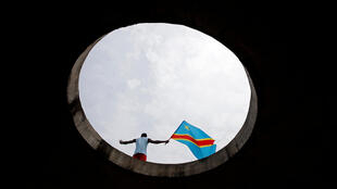 FILE PHOTO: A supporter of Martin Fayulu, runner-up in Democratic Republic of Congo's presidential election holds the Congolese flag during a protest in front of the constitutional court in Kinshasa, Democratic Republic of Congo, January 12, 2019