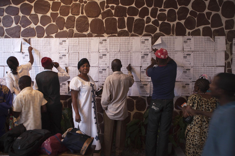 Des électeurs cherchent leur nom sur les listes électorales dans un bureau de vote de Kinshasa, capitale de la République Démocratique du Congo.