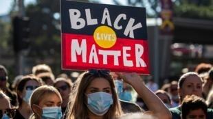 """Une manifestante brandit une pancarte """"Black lives Matter"""" lors d'une manifestation à Brisbane, en Australie, le 6 juin 2020."""