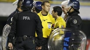 Referee Dario Herrera had to be escorted from the pitch by riot police after he called off the Copa Libertadores game between Boca Juniors and River Plate.