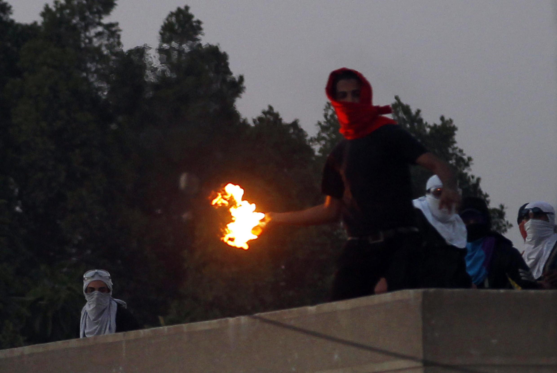 Des étudiants proches des Frères musulmans lancent des cocktails molotov sur les forces de l'ordre, le 27 décembre 2013 au caire.