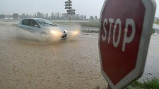 A motorist drives his car through water during a storm in Burnhaupt-le-Haut, eastern France, on June 4, 2018.