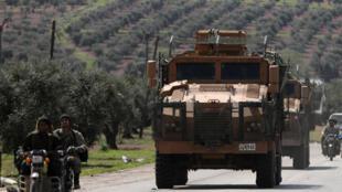 Thành viên lực lượng Syria Tự Do đi xe gắn máy, cạnh đó là một xe quân sự của Thổ Nhĩ Kỳ, ở Afrin, Syria, ngày 19/03/2018.