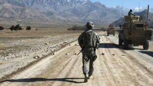 Un soldado de EEUU camina tras unos vehículos blindados por una carretera en construcción cerca de Bagram, el 11 de enero del año 2010 a unos 60 km de Kabul