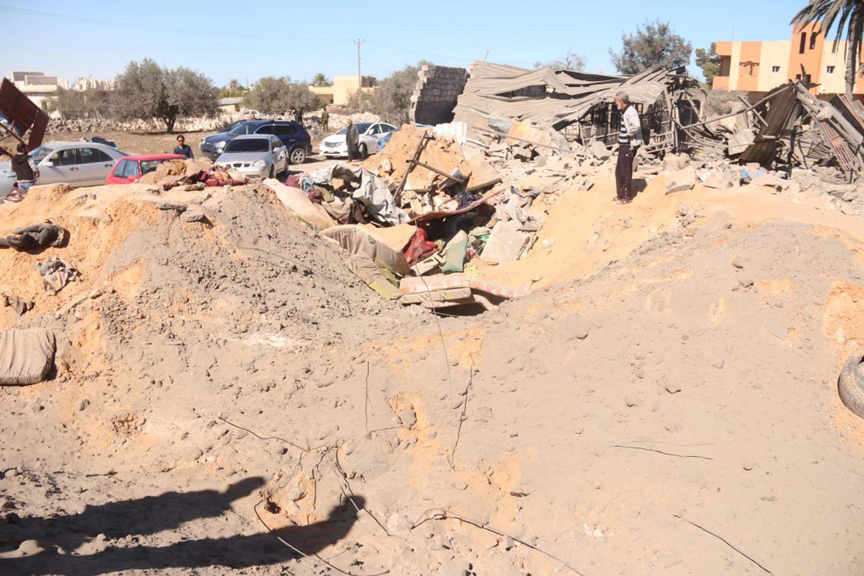 Moradores observam buraco deixado por explosões americanas em Sabratha, na Líbia.