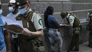 Una policía chilena informa a los extranjeros sobre los pasos para solicitar residencia, el 12 de abril de 2021 en Santiago