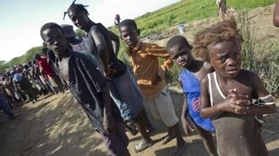 Children wait to receive bottled water in Jurve, a small village on the Artibonite River, Haiti