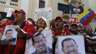 Wasu magoya bayan shugaba Hugo Chavez rike da hotunansa