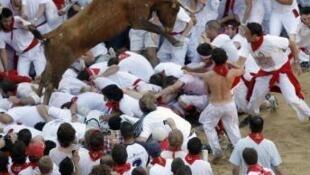 A multidão corre dos touros pelas ruas de Pamplona.