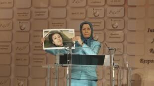 مریم رجوی عکس فردی که درکمپ اشرف کشته شده رابه جمعیت حاضردرمیتینگ سازمان مجاهدین درحومۀ پاریس نشان می دهد