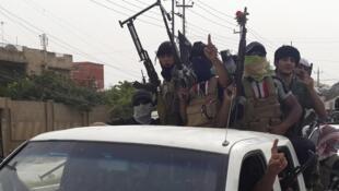 Des combattants de l'Etat islamique en Irak et au Levant, dans une rue de Mossoul, le jeudi 12 juin.