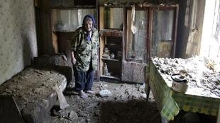 An elderly woman inspects debris while standing inside her damaged house on the outskirts of Donetsk.