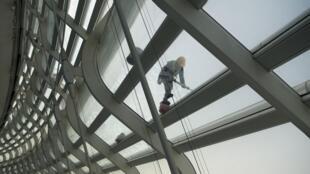 Un trabajador limpia el techo de un estadio en el parque olímpico en Pekín, en marzo de 2021, afinando los preparativos para la competencia