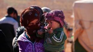 (photo d'illustration) Une réfugiée tient son bambin dans les bras. Pour les femmes déplacées, l'exil a rendu plus difficile l'accès aux soins maternels et parfois bouleversé leur désir de maternité.