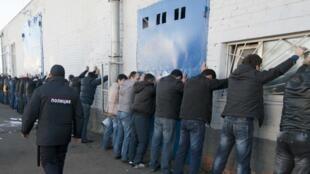 Cảnh sát Matxcơva vừa bắt giữ những người lao động nhập cư trong một cuộc truy quét tại khu phố Biryulyovo, 14/10/2013.