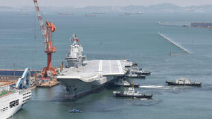 图为中国自制航母002号试水返航停泊大连船厂港口