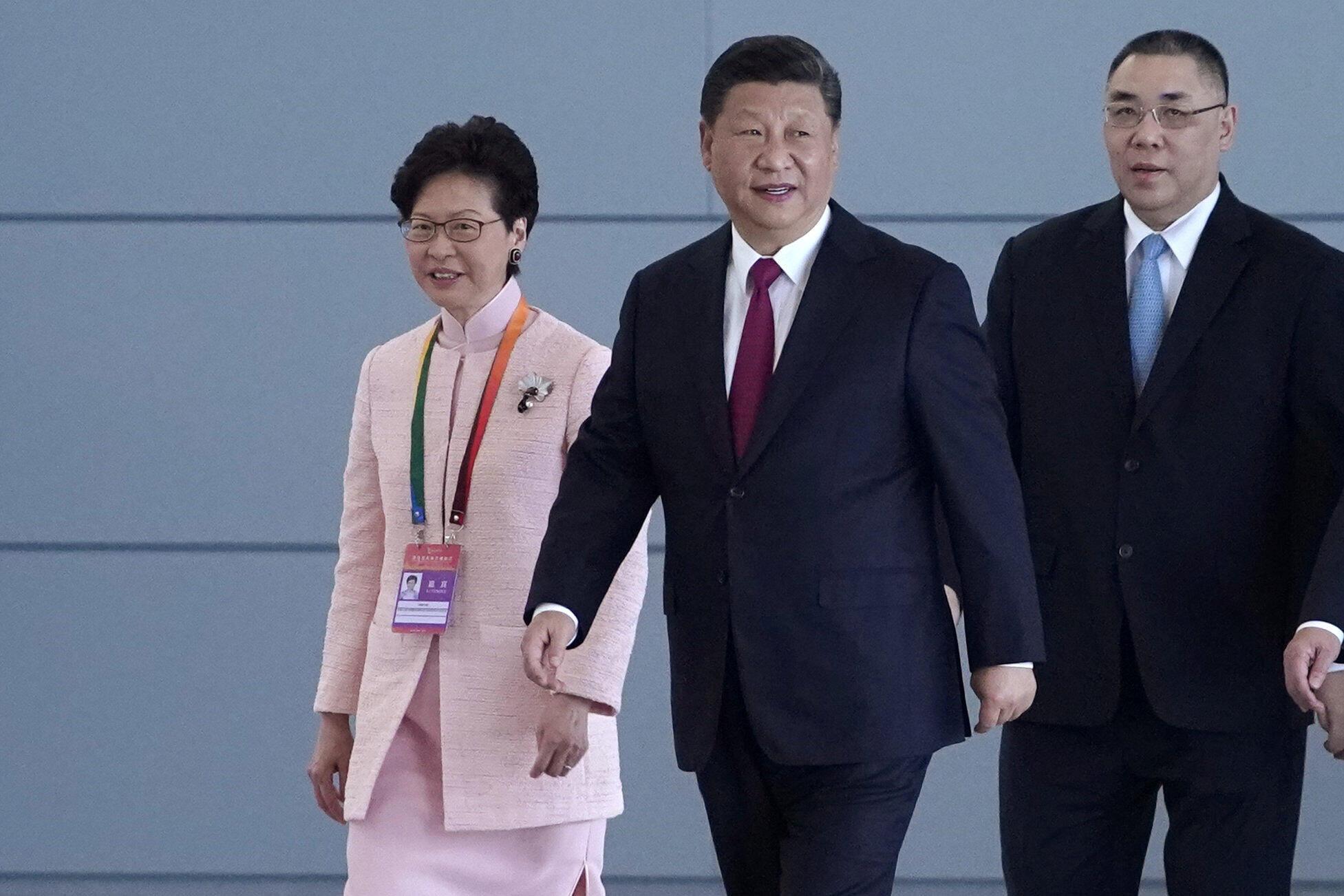资料图片:2018年10月23日,澳门特首崔世安(右)与香港特首林郑月娥(左)陪同中国国家主席习近平出席珠港澳大桥通车剪彩仪式。
