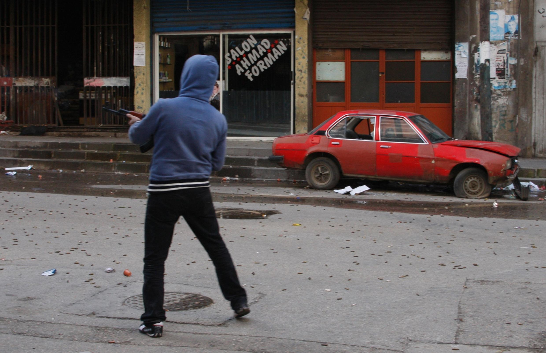 Jovem armado atira entre os bairros sunitas e alauítas da cidade libanesa de Tripoli.