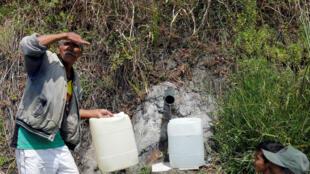 Personas hacen la cola para llenar bidones con agua de una corriente de agua en una montaña en Caracas, el 13 de marzo de 2019.