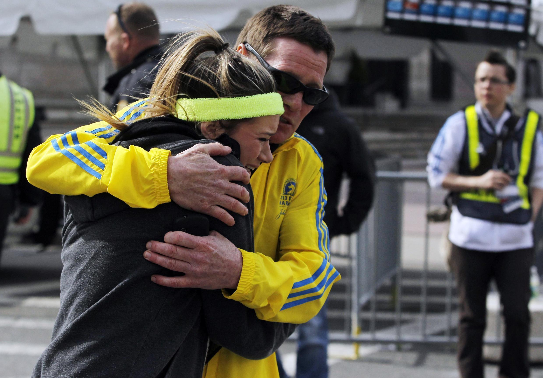 Maratonistas chocados recebem apoio após as explosões em Boston.