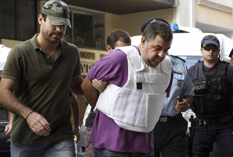 Les policiers encadrent George Roupiakas lors de son transfert au tribunal.