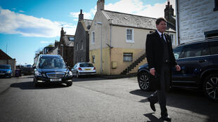 A funeral director leads the hearse carrying the coffin of care worker Janet Livingston, who died of COVID-19, through her home village of Ferryden in Scotland