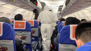 Agentes verifican el estado de salud de los pasajeros en un avión de Shanghai, 25 de enero de 2020.