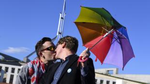 Casal comemora do lado de fora do Parlamento australiano nesta quinta-feira (7).