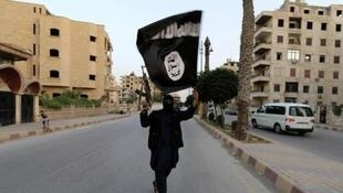 An Islamic State militant carries the armed group's flag on the streets of Raqqa, Syria, 29 June 2014