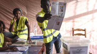 Un agent électoral tend un bulletin de vote dans un bureau de Bissau, le 10 mars 2019.